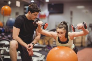 Gym instructor helping a woman