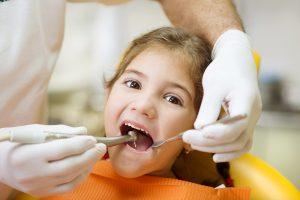 Dentist checking child patient's teeth