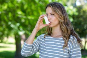 Woman using inhaler at the park