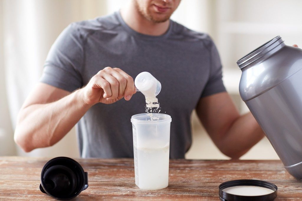man preparing whey protein drink