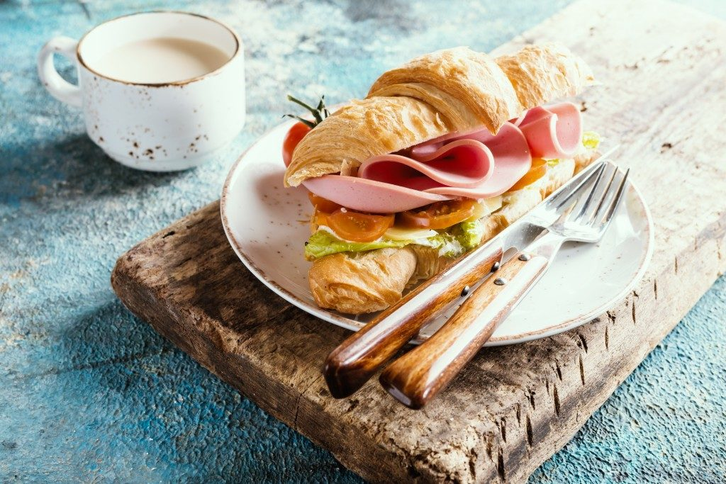 Fresh croissant sandwich with ham, cheese and salad leaf with coffee on blue table