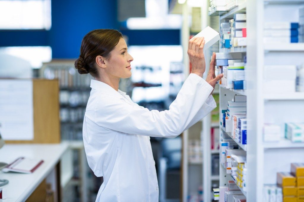 Pharmacist putting medicines on the rack