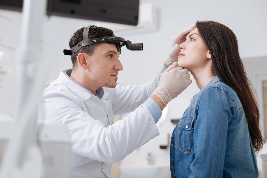 ENT doctor checking the nose of a patient