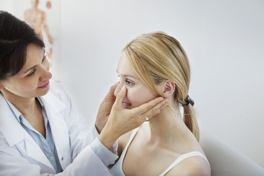 doctor checking the nose of a woman