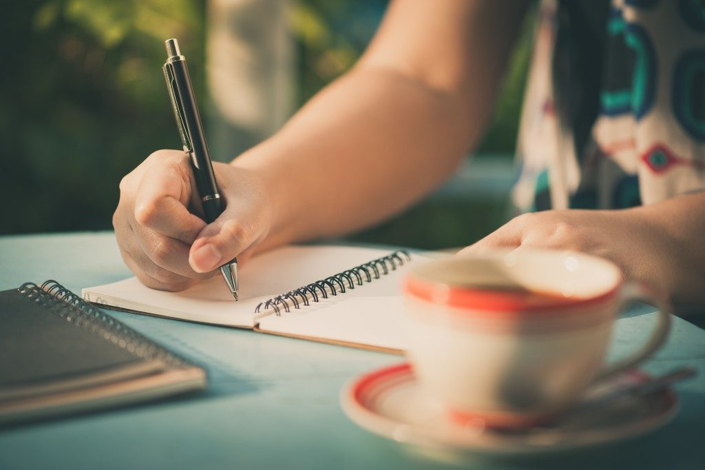 Woman hand writing journal on small notebook at outdoor area in cafe