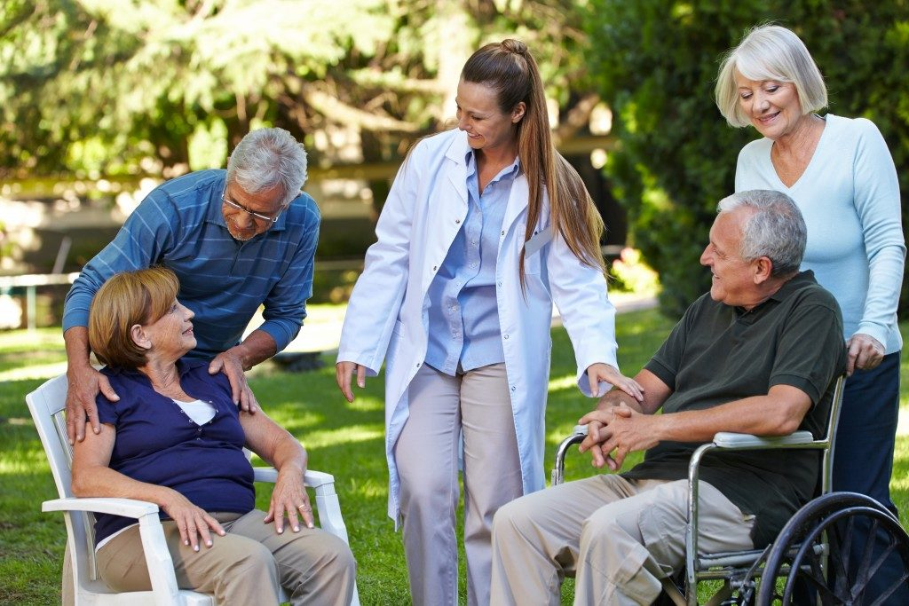 seniors relaxing in a park of a nursing home with geriatric nurse