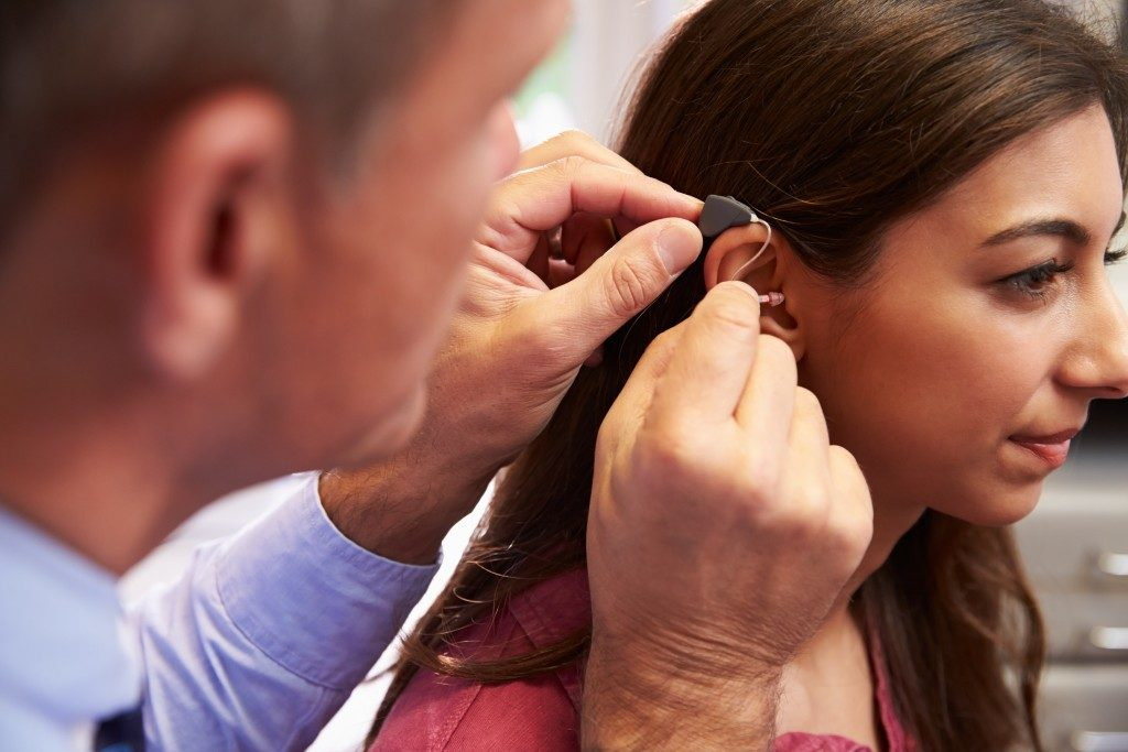 doctor fitting  the hearing aid