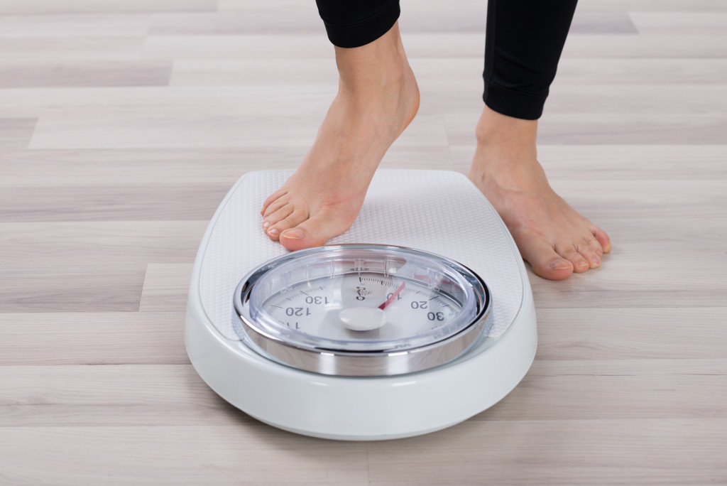 person stepping on a weighing scale